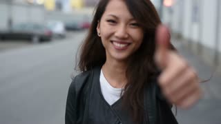 young asian woman smiling with thumb up