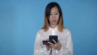 young asian woman using smartphone for buying online or pay order or bills on blue background in studio. attractive millennial girl wearing white casual shirt looking at the camera smiling