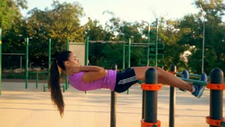 Young athletic woman doing push-ups on a horizontal bar on a summer sunny day at the stadium, rear view. Slow motion