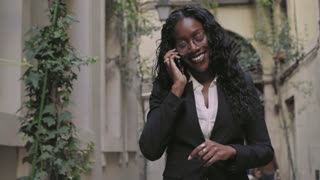 Young attractive african american natural beauty woman in business casual outfit , walks on street, talks on phone, smiles and laughs confident and independent empowered female