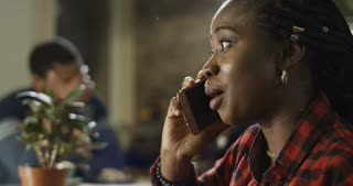 Young attractive black woman talk on her mobile phone indoors in a cafeteria in a close up profile view