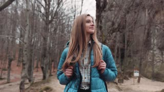 Young attractive blonde girl in a casual outfit with a backpack, walking through the deserted forest and enjoying the beautiful autumn nature. No people around.