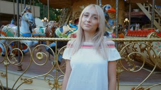 Young attractive blonde girl standing near carousel in amusement park. Beautiful portrait of woman with long hair. Slow motion