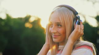 Young beautiful blonde listening to music with headphones in the park on sunset background. Slow motion. Lovely woman