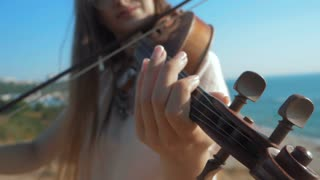 Young beautiful caucasian girl wearing jeans plays violin staying on the beach near the beautiful sea or ocean, Slow motion
