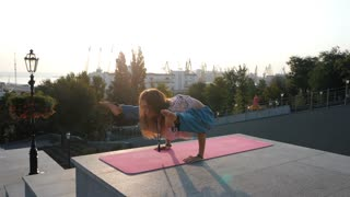 Young beautiful caucasian woman doing yoga asana in the city. Summer morning. Girl wearing blue pants, pink lace t-shirt and mala beads for meditation. Slow motion