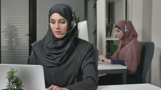 Young beautiful girl in black hijab with headset answers a call center. Arab women in the office. Concept 60 fps