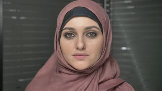 Young beautiful girl in pink hijab smiling and looking at camera. Portrait, close up 60 fps