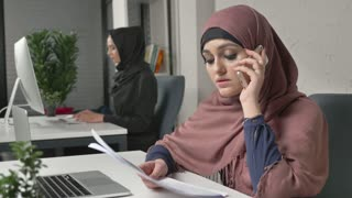 Young beautiful girl in pink hijab working with documents and talking on mobile phone. Arab women in the office. 60 fps