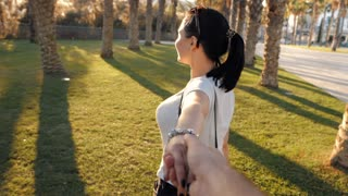 Young beautiful girl leading a man forward to the summer adventure. Woman enjoys traveling in tropical vacation with palm trees. Follow me concept. Slow motion