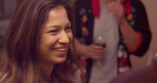 Young beautiful woman laughing at a holiday party. Slow motion.