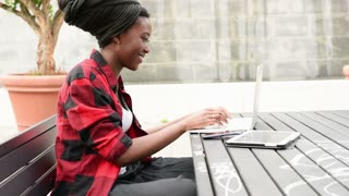 Young black businesswoman using several devices