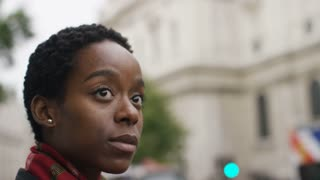 Young black woman waiting to cross the road in the street, in slow motion