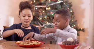 Young boy and girl stuff their faces full with cookies on Christmas.