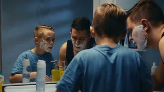 Young boy learning to shave helped by his father as they peer at their reflections in a bathroom mirror with chins covered with shaving foam as the youngster tries out a razor.