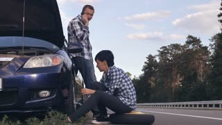 Young caucasian woman changing a tire on the side of the road. Man using mobile phone talking with friend