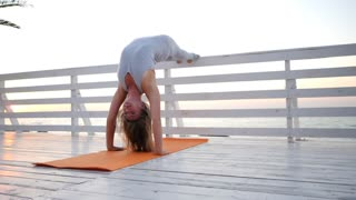 Young caucasian woman doing yoga asana in the nature on a wooden bridge overlooking sea. Woman doing practice on the ocean relaxing in nature. Girl in sport bodysuit. Slow motion