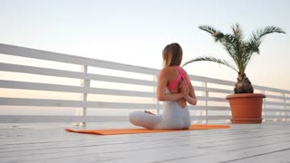 Young caucasian woman doing yoga namaste in the nature on a wooden bridge overlooking sea. Woman doing practice on the ocean relaxing in nature. Girl in sport bodysuit. Slow motion
