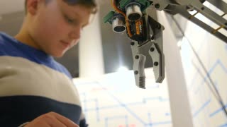 Young child playing with robotic arm