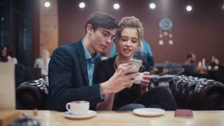 Young couple taking self-portrait photo kissing, laughing and enjoying each other having a date in an urban café.