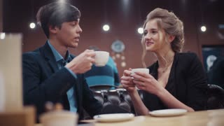Young couple talking and drinking coffee on a date in a modern restaurant.