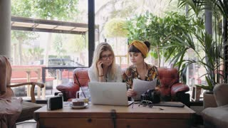 Young creatives, freelance workers, blonde and brunette pretty women, discuss and plan new project during meeting in trendy downtown cafe, have call on smartphone, point to laptop images