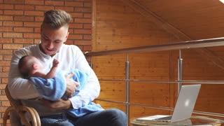 Young father rocking his adorable baby son while working on computer at home