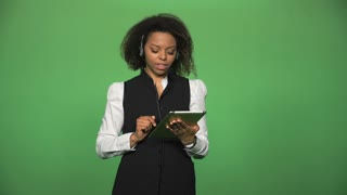 Young female in formal suit wearing headset and holding tablet ready for customer supporting in in call center emotional talking with customer