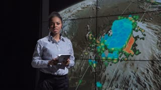 Young female researcher making report about hurricane origin and explaining its reasons using screen with images. Elements of this image furnished by NASA