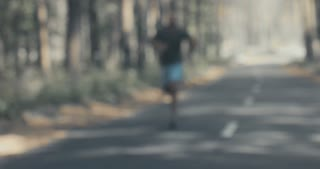 Young fit African American man sweating while catching breath after sprinting on the forest road. 4K UHD
