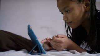 Young girl using a digital tablet whilst relaxing on her bed