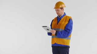 Young good looking male builder or construction worker with tablet PC looks at camera, smiles and raises up the thumb