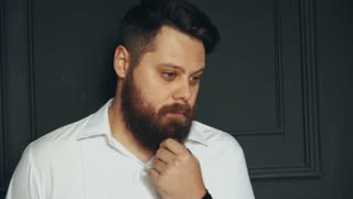 Young handsome bearded man on serious face in studio