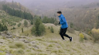 Young handsome man in blue jacket running in autumn nature