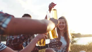 Young happy friends in casual wear toasting with bottles of beer while being at picnic, laughing happily. Beautiful nature, summer season. True emotions, positive mood.