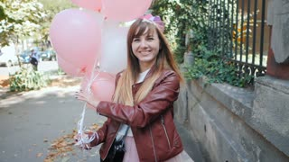 Young happy woman with paper crown, colourful white and pink baloons smiling and laughing. Birthday girl walking on the street to camera. Slow motion