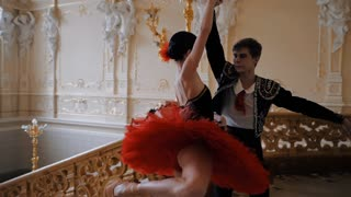 Young man dancing classical ballet with young beautiful woman in red tutu in the theater foyer. Amazing interior, sensual dance. Slow motion. Dolly shot. Adagio