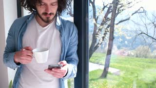 Young Man Drinking Coffee And Using Smartphone By The Window