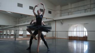 Young man practicing in classical ballet with young beautiful woman in black clothing in the gym. Minimalism interior, sensual dance. Slow motion