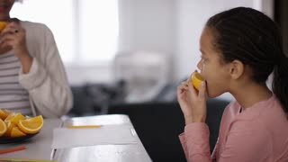 Young mother or childminder talking to two children as they eat a fruit snack