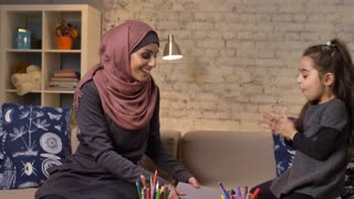 Young Muslim mother in a hijab takes a book in her hands, her daughter enthusiastically laughs and claps her hands 50 fps