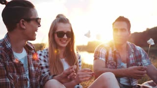 Young people having the picnic by the riverside, laughing happily, eating fried marshmallows and drinking beer. Having a little party. Friendship goals, summertime evenings. Positive atmosphere.