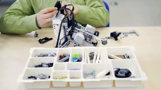 Young school boy assembling model kit of a futuristic robot. 4K.
