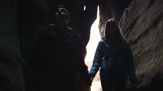Young tourists studying the dark cave, holding their hands, and moving towards the camera.