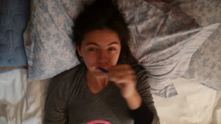 Young Woman Brushing Her Teeth While Laying In Bed