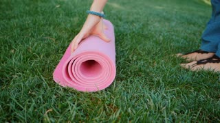 Young woman doing yoga exercise - opening her pink yoga mat on green grass at the park. Slow motion