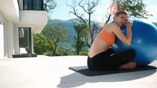 Young Woman Doing Yoga in front of villa