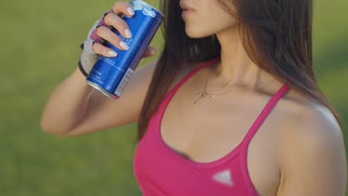 Young woman drinking energy drink. Asian woman drinking soda. Sport woman drinking energy drink. Closeup of asian girl holding soda can. Sporty woman drinking energy drink outdoors