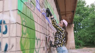 Young woman graffiti artist drawing on the wall, exterior