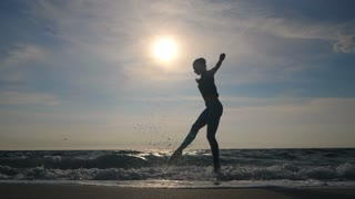 Young woman in casual style - denim and black top doing ballet at the beach. Attractive ballerina practices in stretching on sandy coastline in autumn. Slow motion